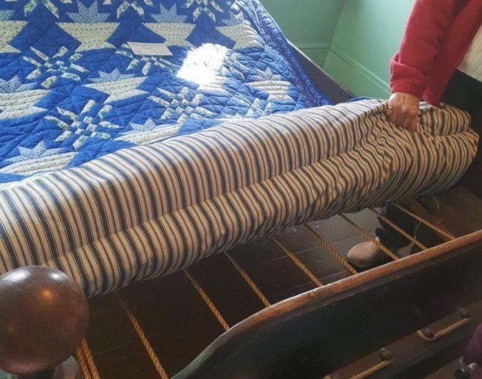 מיטה מחבלים, מזרן מנוצות, שמיכה רקומה עבודת עקרת הבית.
