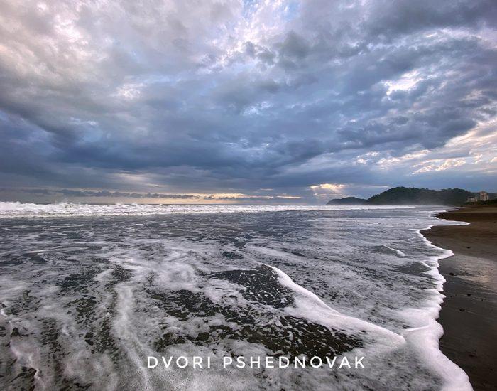 גלים שהופכים לקצף על החוף הרחב